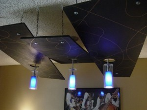 Geometric panels hanging from ceiling with pendent lighting. 2