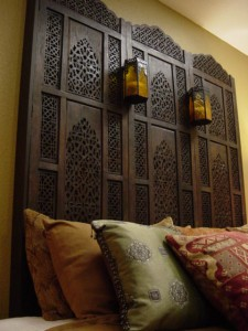 Old world room divider mounted on wall as a headboard with candles. 1