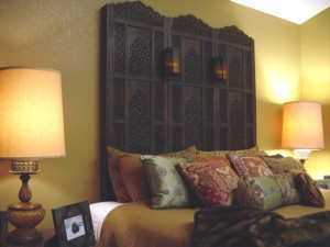 Old world room divider mounted on wall as a headboard with candles. 2